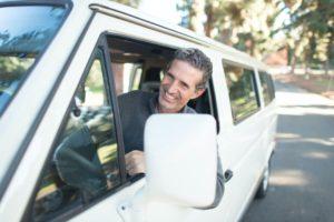Homem feliz em um van com o braço fora da janela